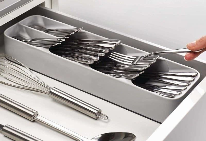 A person putting a fork inside the cutlery organizer inside the drawer
