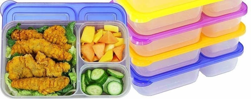 The bento boxes with one filled with chicken in the big compartment, and fruit and veggies in the two smaller compartments