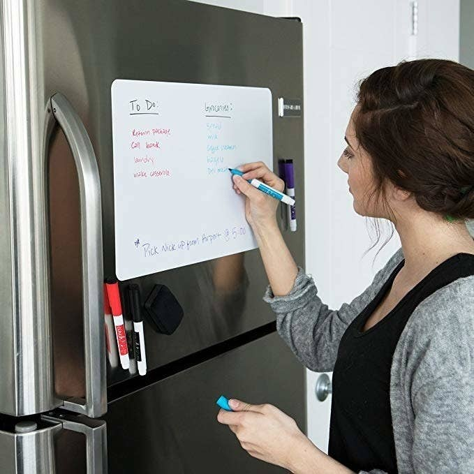 person writing on magnet erase board hung on fridge