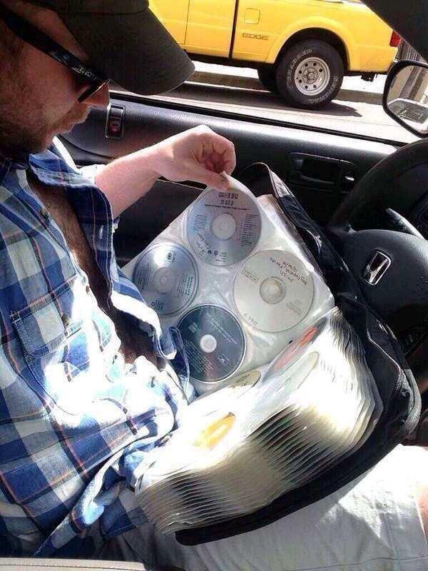 a man looking through a big CD binder