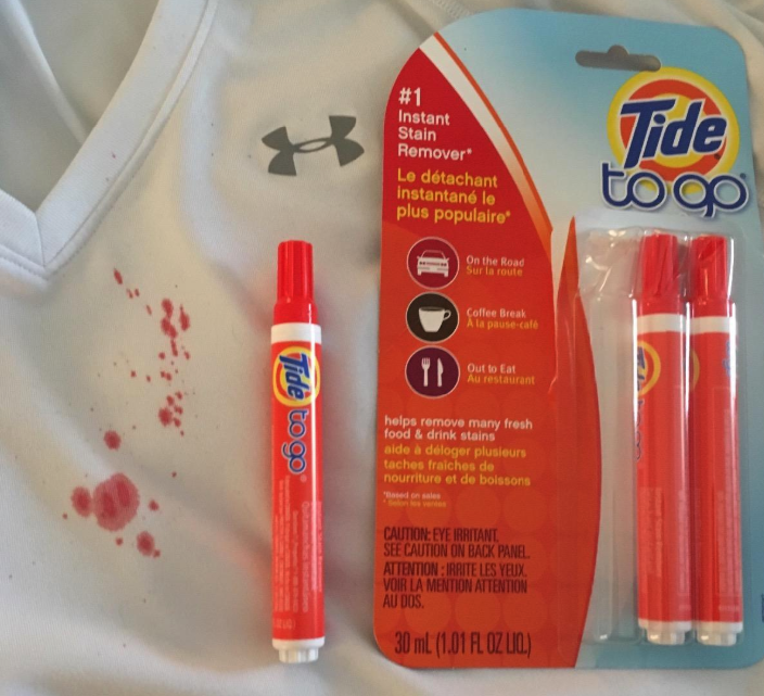 A reviewer image of the Tide To Go pen next to a stain on an athletic shirt