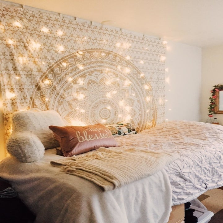The string lights draped down a wall by a bed
