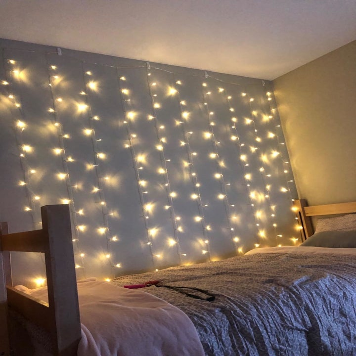 The string lights draped down a wall by a bed in the dark