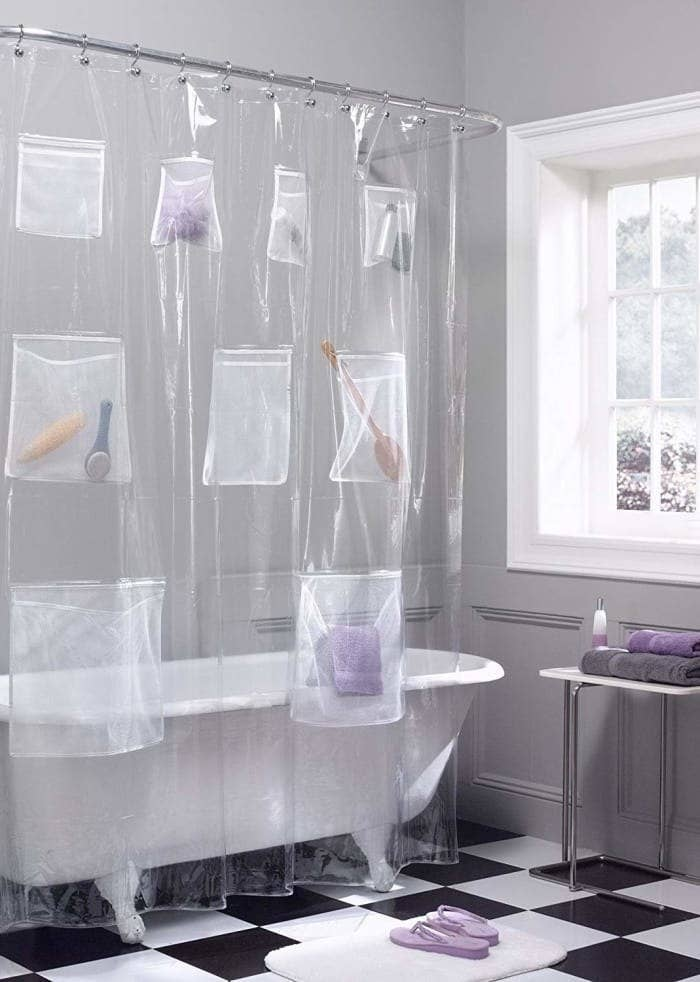the shower curtain with bath accessories stored in the pockets