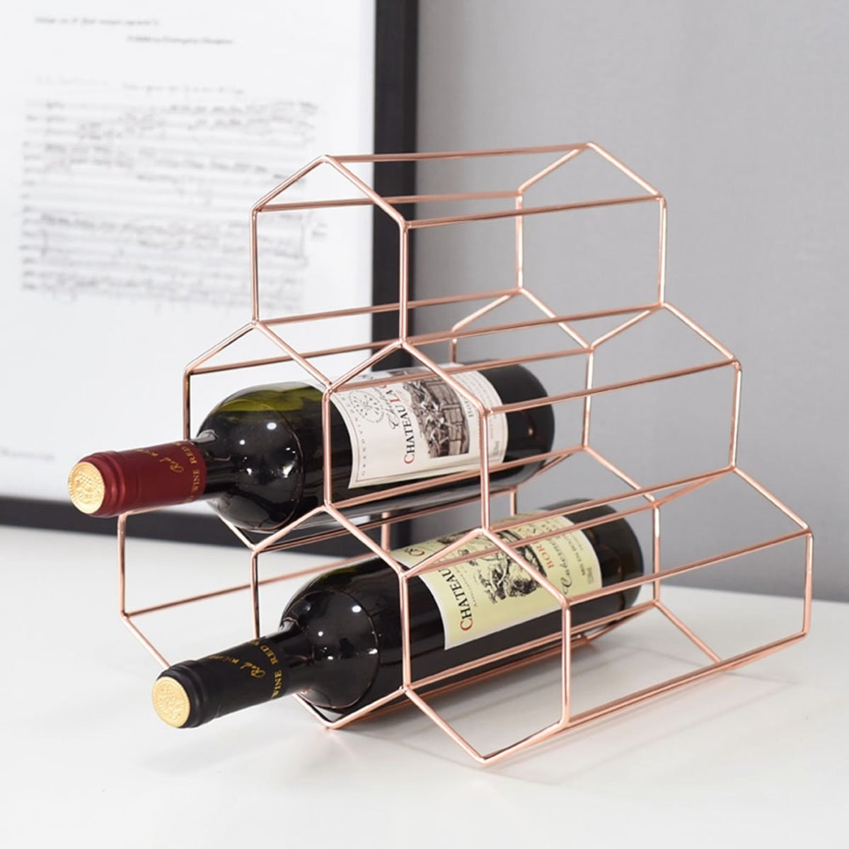 The rose gold honeycomb pyramid wine rack on the counter with two bottles of wine in it