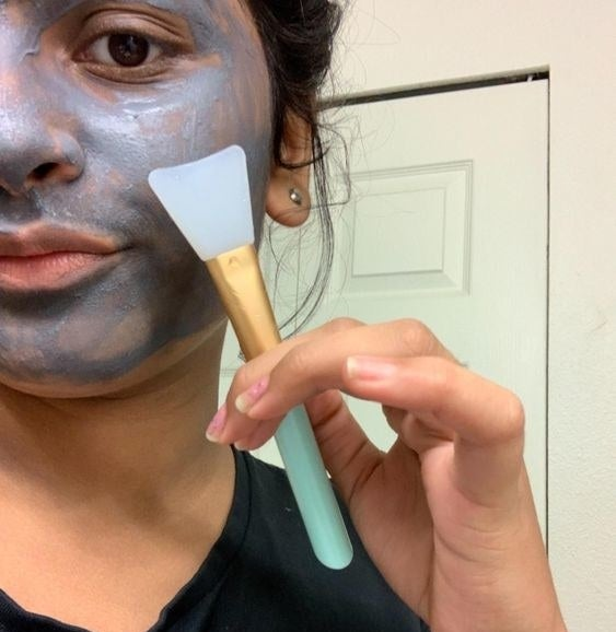 Reviewer using the brush to apply a charcoal face mask