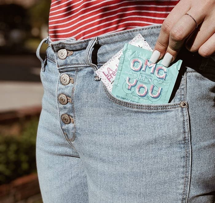Model pulling out a small packet of the La Fresh wipes from their jeans pocket showing its convenient travel-friendly size