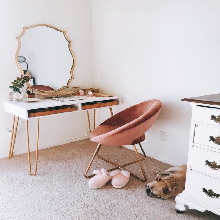 Reviewer pic of the pink chair in front of a vanity