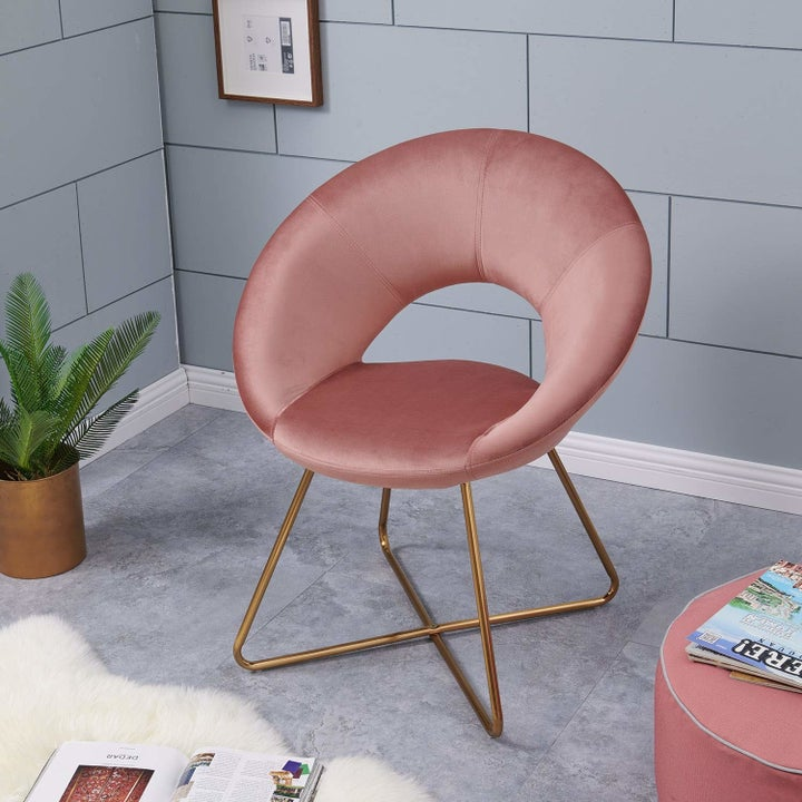 Closeup of the circular accent chair in pink velvet with gold legs