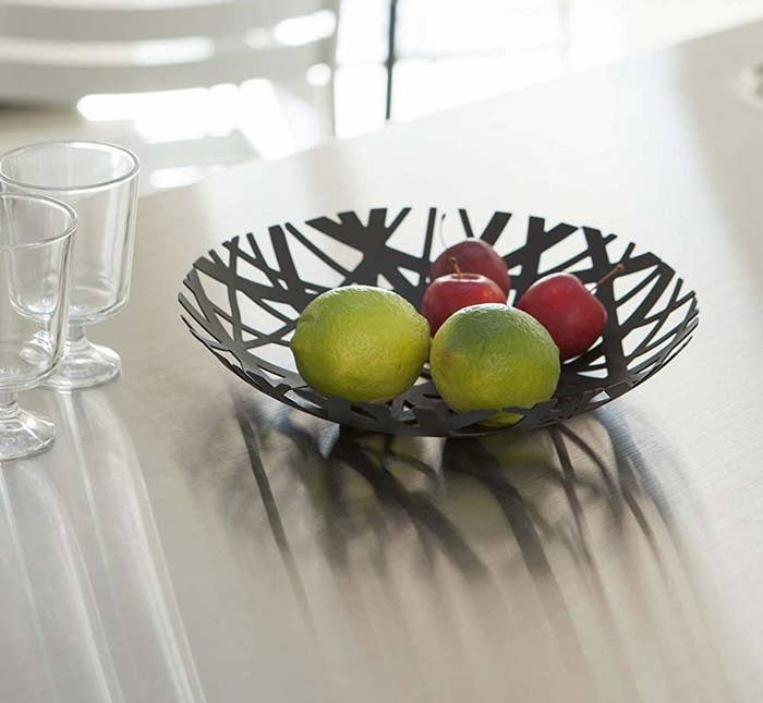 Black bowl made of crisscrossing stripes with openings and assorted limes and other fruit inside