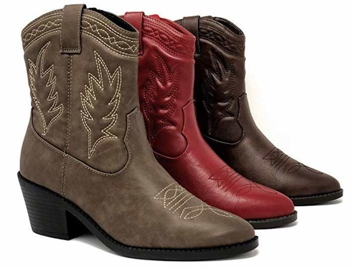 three cowboy boots that come up just above the ankle but just below the calves. They ahv a pointed toe and embroider on the side. The three boots are brown, deep brown, and red.
