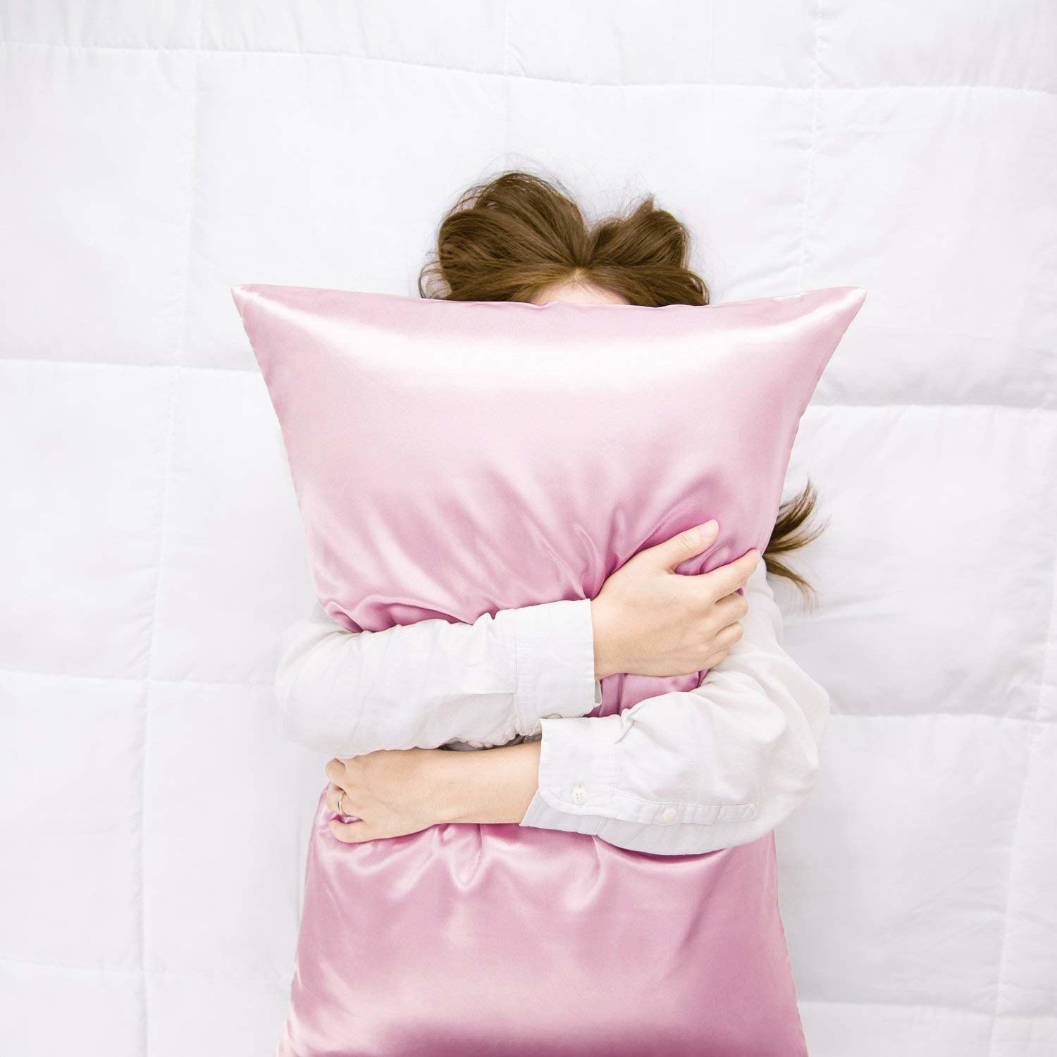 person hugging a pillow with the satin pillowcase on it
