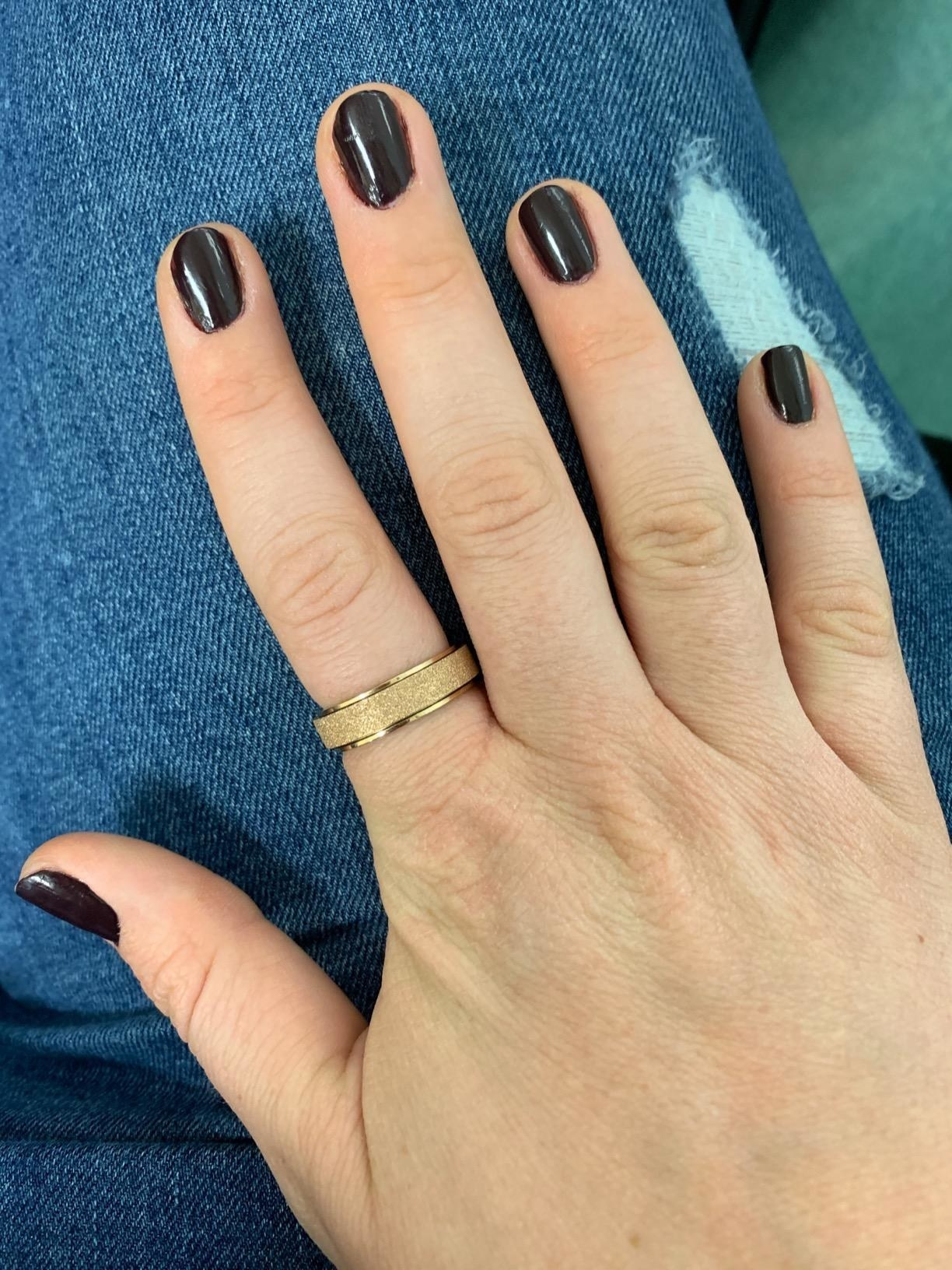 A reviewer showing the ring around their finger in gold