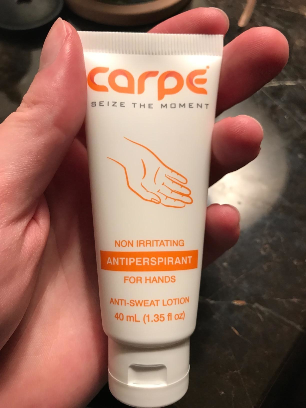 A reviewer holding a tube of lotion