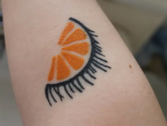 "A symbolic tattoo for ""A Clockwork Orange"" of an orange slice with eyelashes"