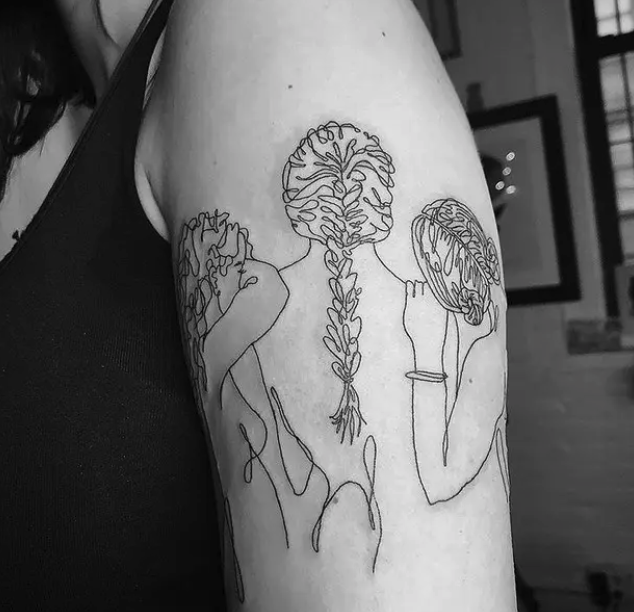 A tattoo of three women with their backs to the camera