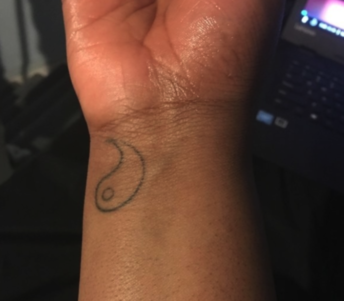 A tattoo of half of a yin-yang symbol