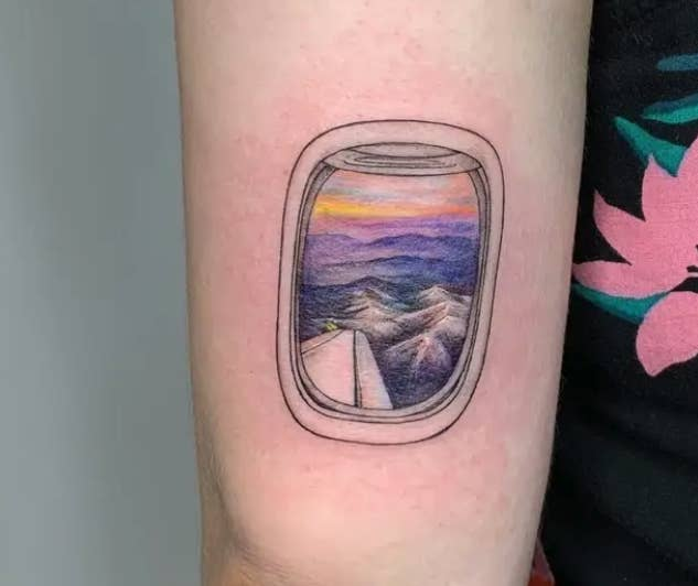 A colorful tattoo of the view from an airplane window on someone's arm