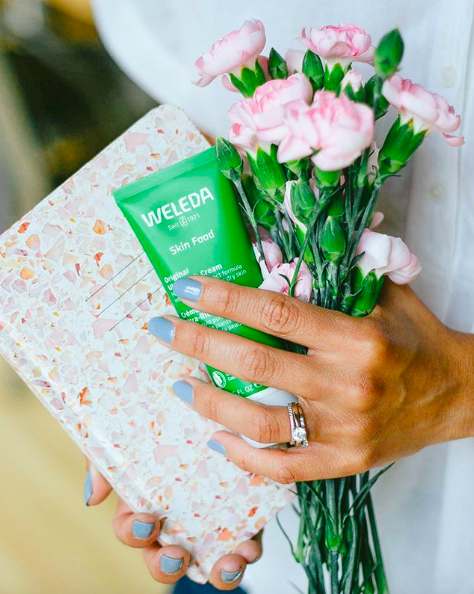 hands holding the moisturizer and flower bouquet