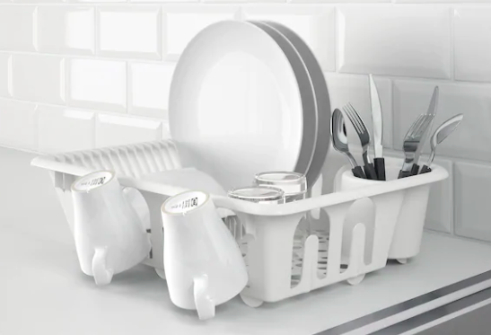 A white dish draining rack placed on a counter with multiple dishes in it.