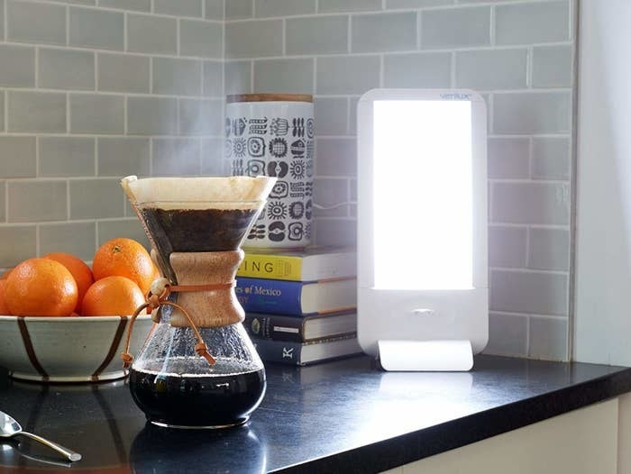 The rectangle-shaped light sitting on the counter with a pour-over coffee next to it