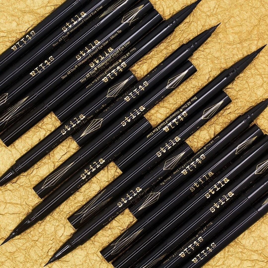 A collection of the eyeliner pens, half with their caps off, showing the thin tip