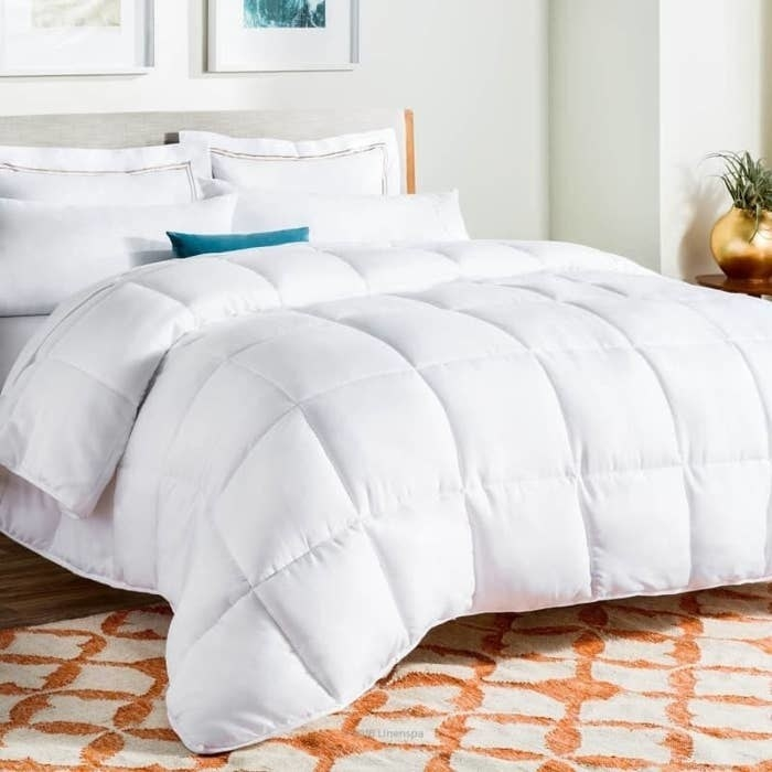 The comforter in white on top of a bed