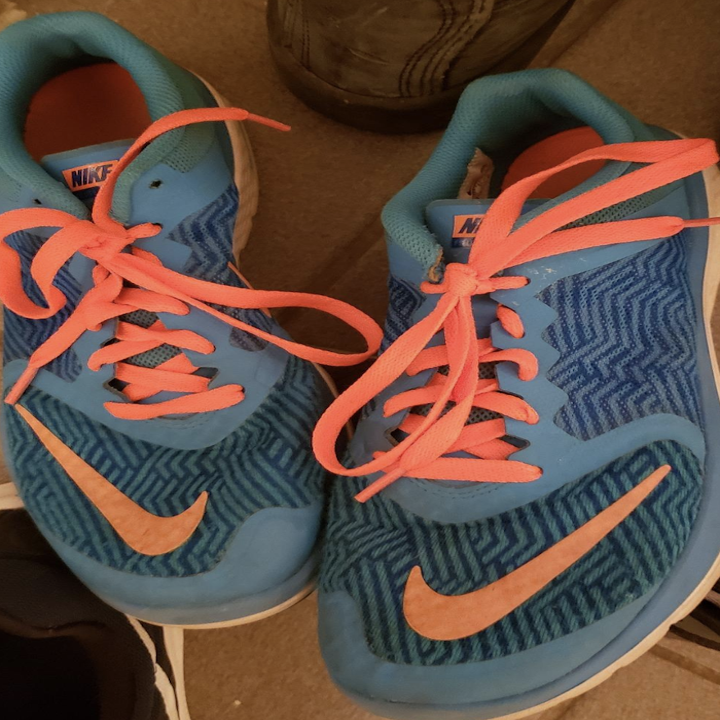 reviewer's pair of sneakers with bright orange laces