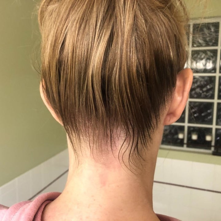 The same person showing their neater, slicked-back bun after using the hair-finishing stick