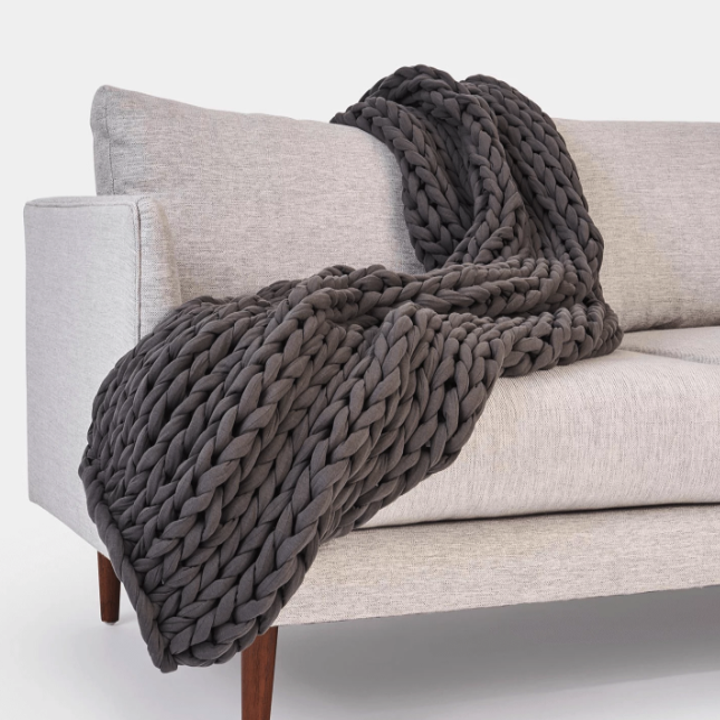 a dark grey blanket on a couch