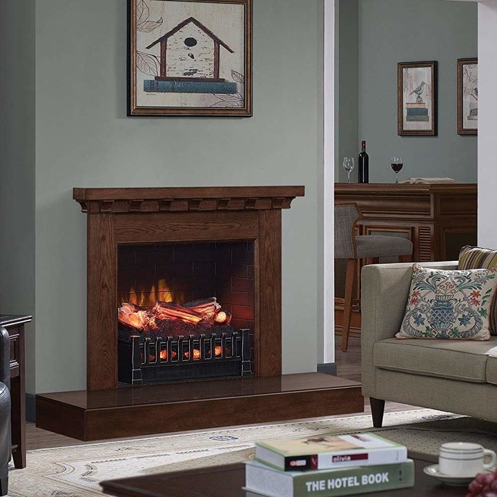 The electric fireplace installed in a fireplace opening in a room