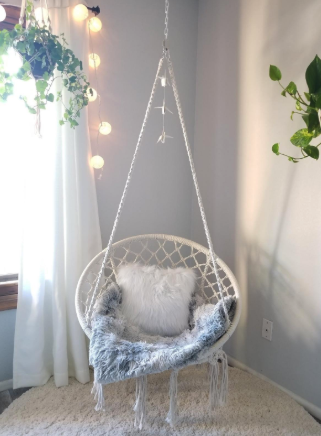 a reviewer's white macrame swing hanging in a corner