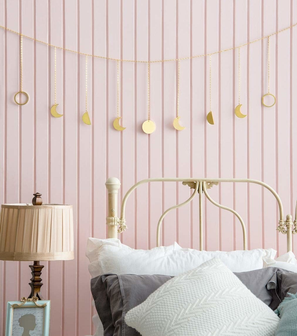 Gold garland with different shaped moons across hanging above a bed