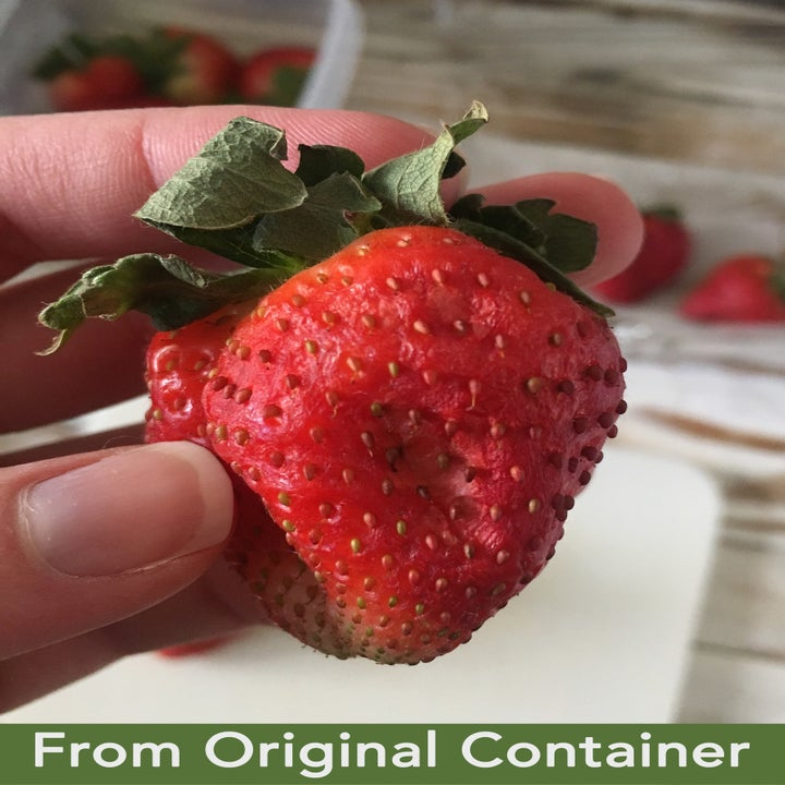 """A hand holding a strawberry that looks slightly-wilted with text that reads """"From Original Container"""""""