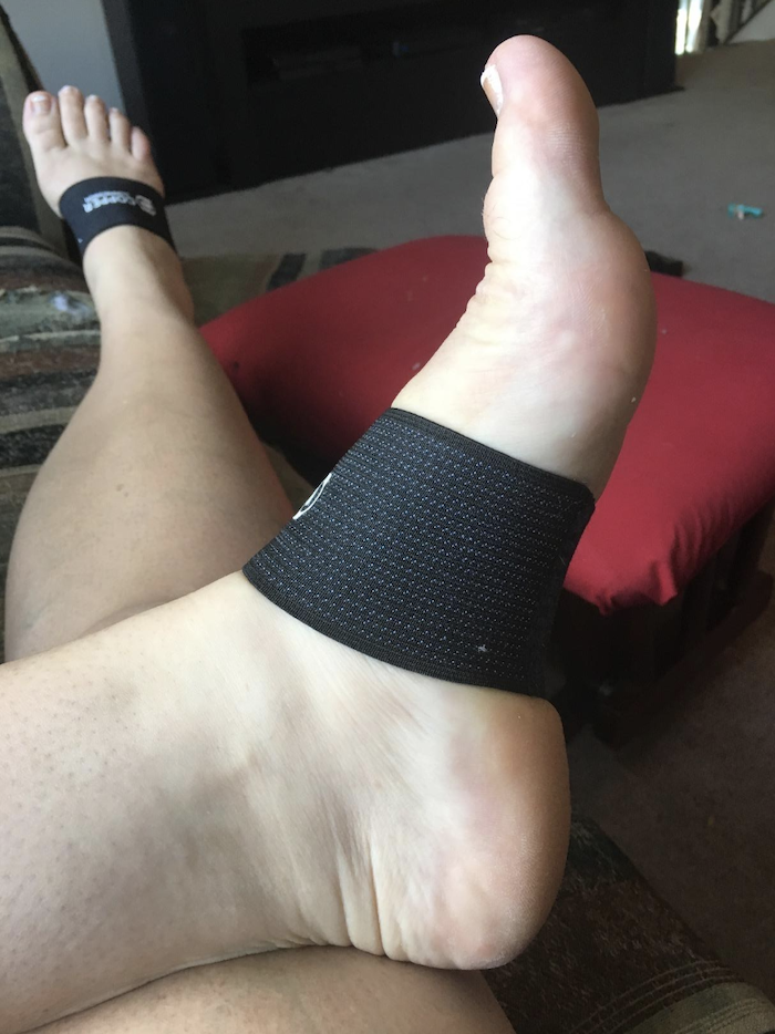 Reviewer with the compression sleeves over the arches of their feet