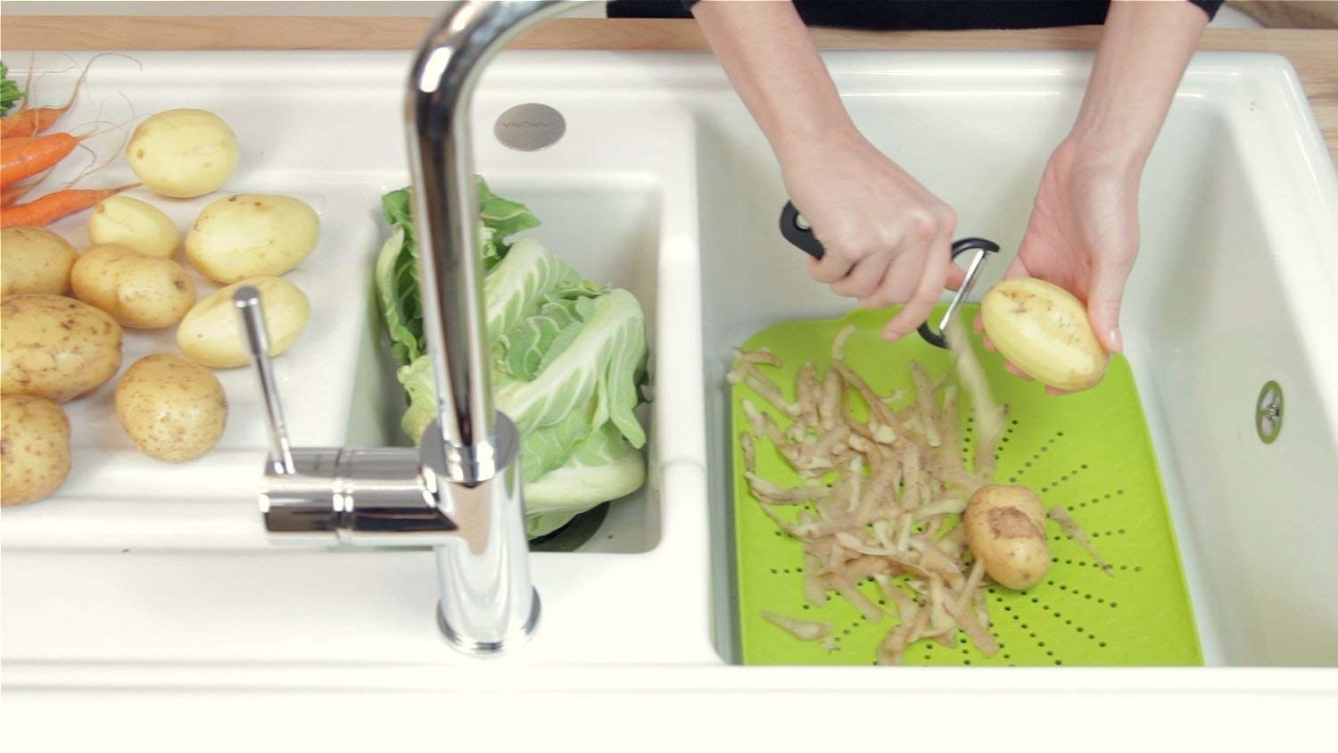 A model peeling potatoes over the green colander in a sink