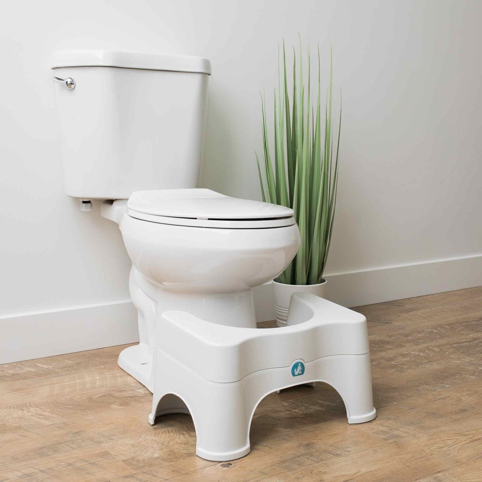 Squatty Potty placed at the foot of the toilet to show that it can easily slide under