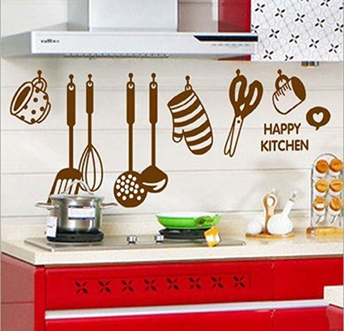 A kitchen decal featuring spatulas, whisks, scissors, cups, and mitts