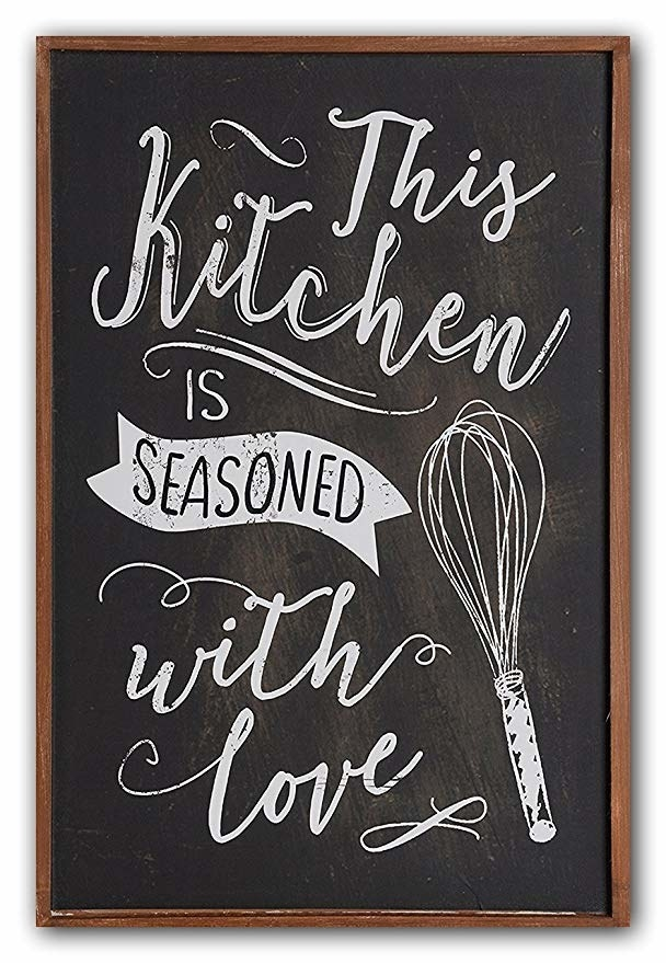 """A chalkboard-style frame with the quote, """"This kitchen is seasoned with love""""."""