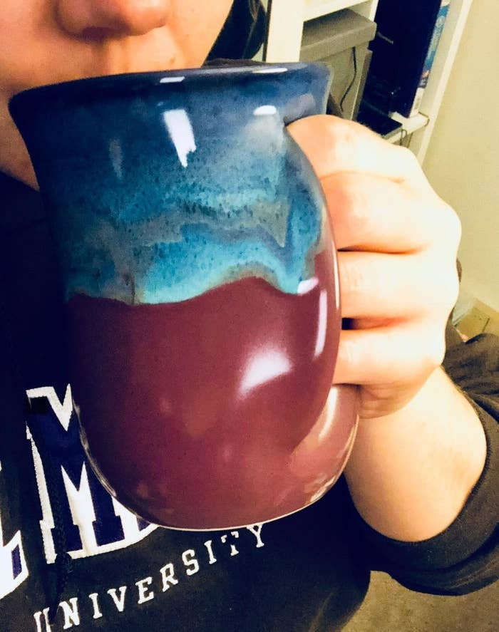reviewer drinking from mug with a pocket on the side for their hand to slide into and grip