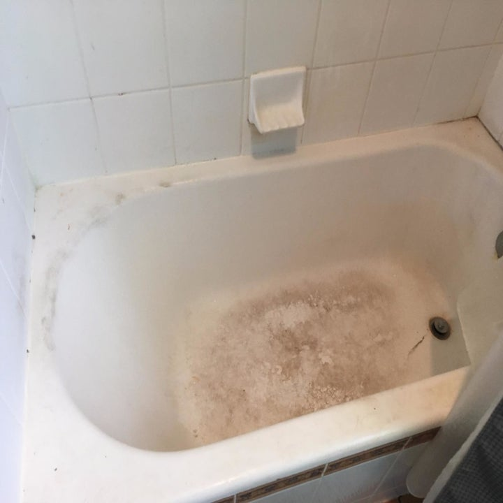 Reviewer before photo of their white tub, which is caked with a brown film