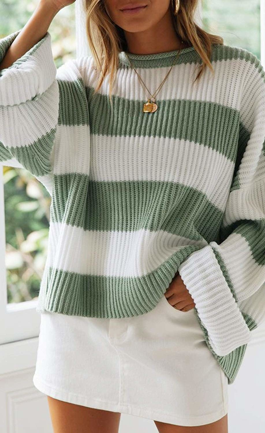 model wears oversized knit sweater with chunky cuffed sleeves and thick stripes