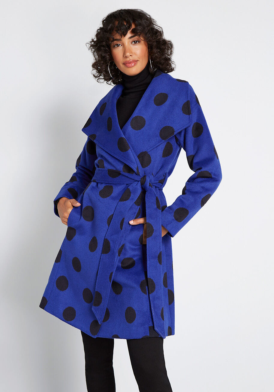 A model wearing the royal blue and black polka dotted coat, which has a tie waist and wide collar and hits at the knee