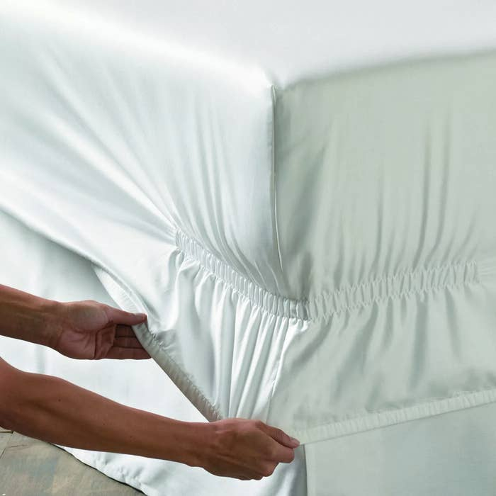 hands pull down fitted sheet with deep pockets