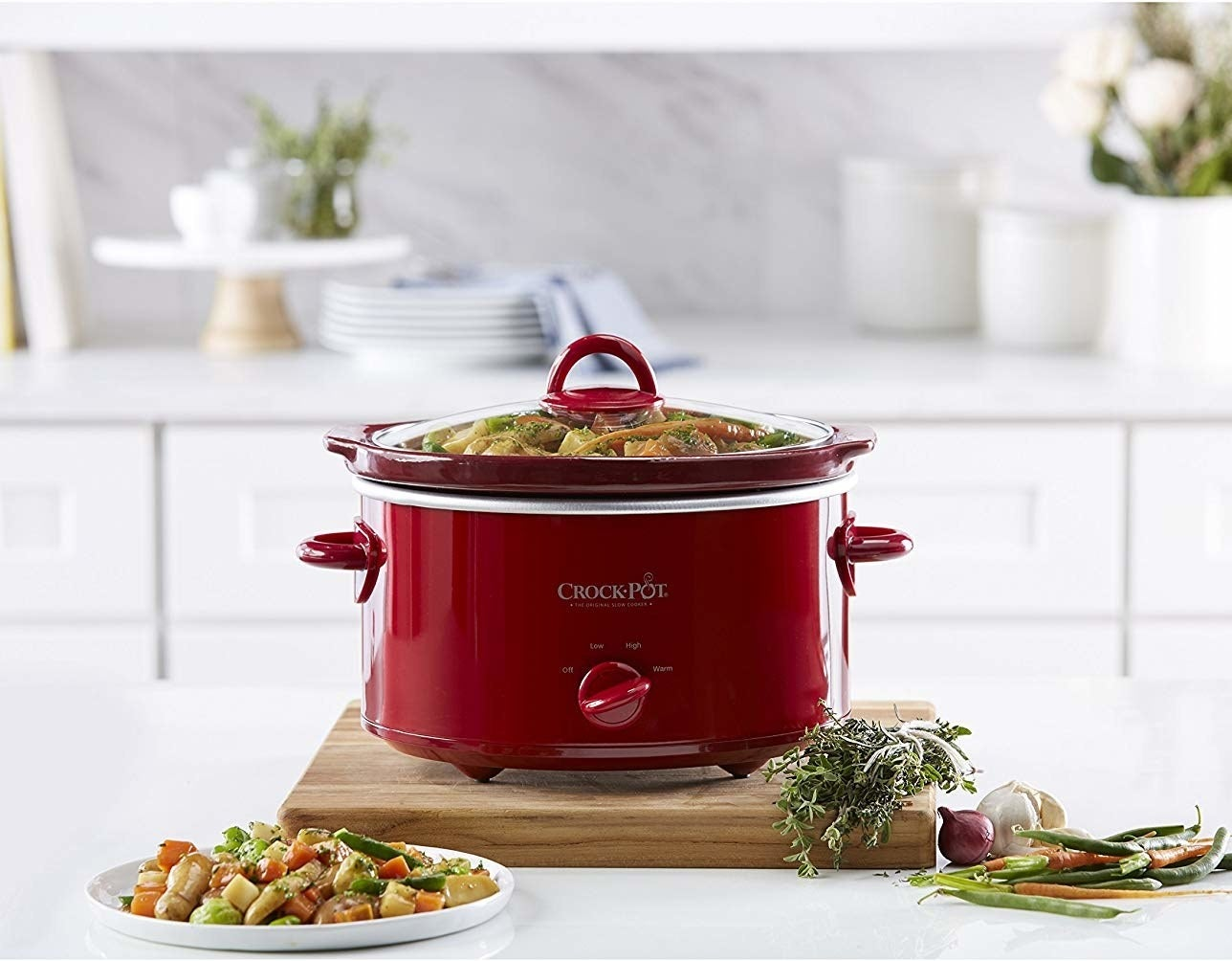 small red crock pot with glass lid