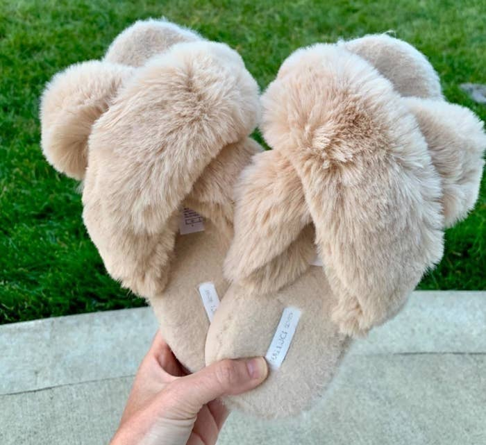 reviewer holding tan fizzy criss cross strap sandal slippers