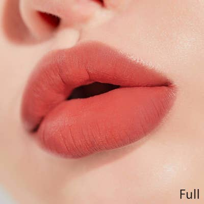 a peachy pink color on full lips
