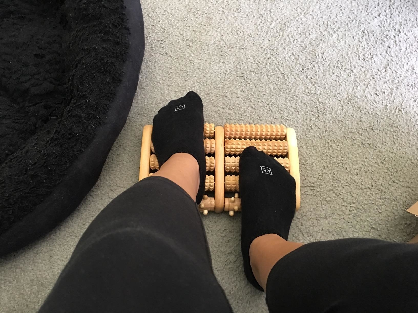 Reviewer rubbing their feet on the textured wooden rollers