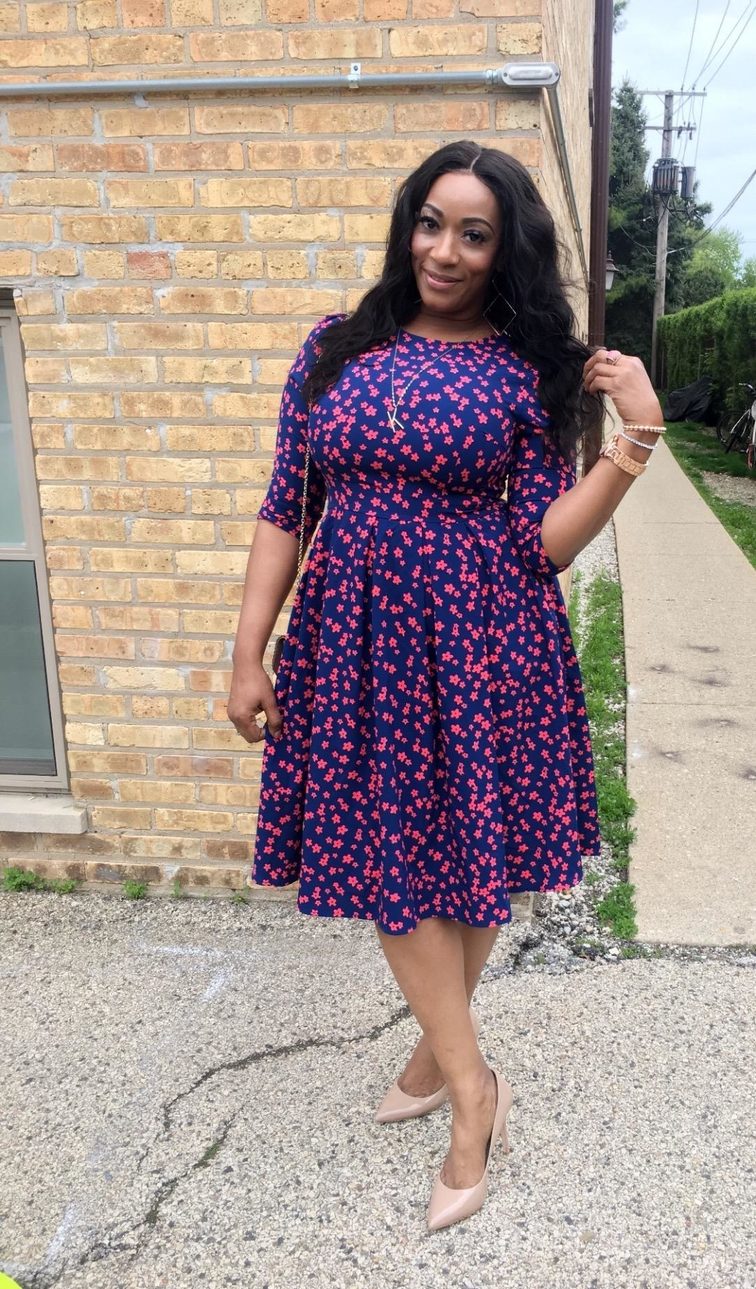 Reviewer wearing the knee-length dress in blue with small red flowers on it