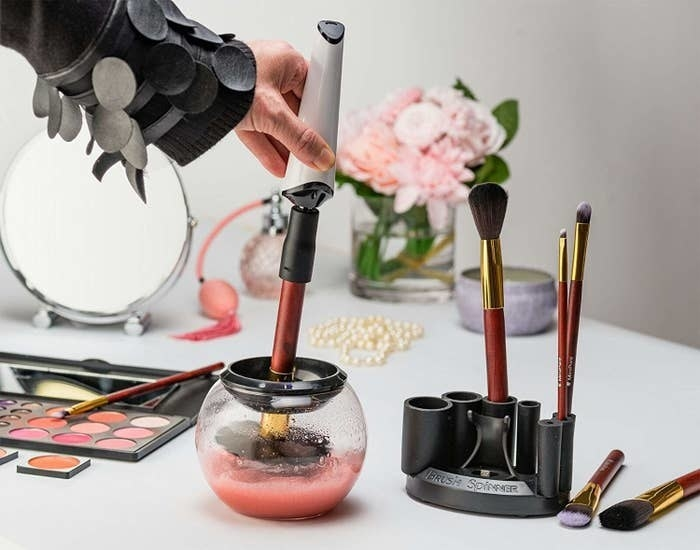 Lifestyle shot of the brush spinner being used to clean a makeup brush. Model is holding the spinner with a makeup brush attached as it spins the brush in a small bowl with cleaning solution.